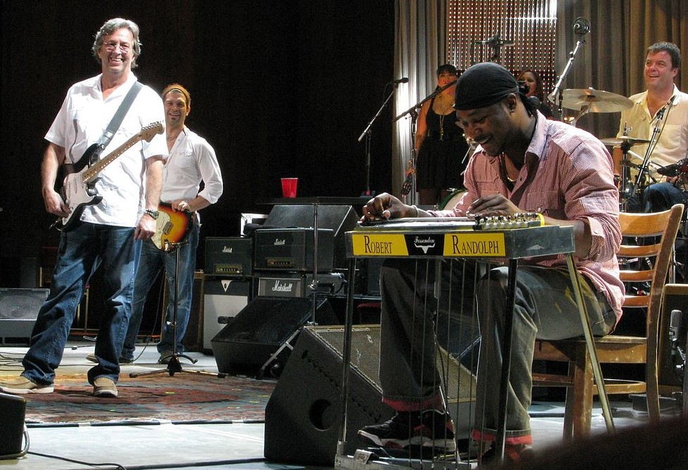 Robert Randolph playing the pedal steel guitar while Eric Clapton looks on. Photo: Steve Proctor via Wikimedia Commons lic.