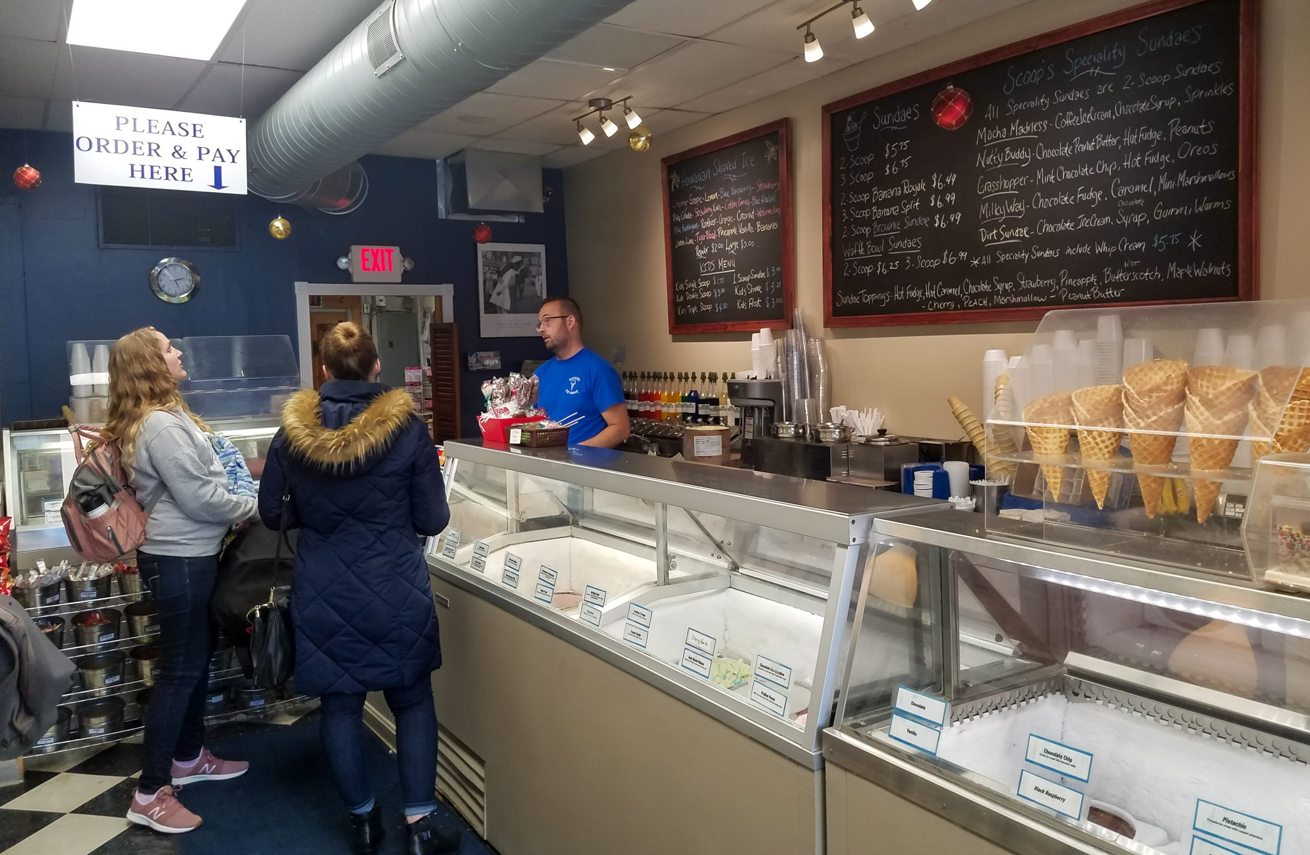 Scoops owner Mike Collins gets the ice cream order from two customers.