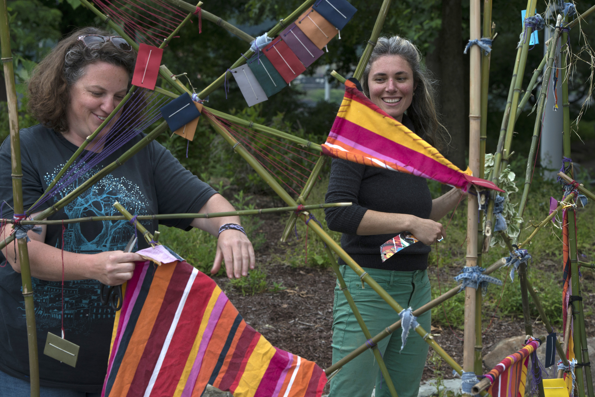 "Assisting artists Jenn Benchak (left) and Jenn Myers (right) add material to Rose Clancy's sculpture ""Diversion"" at Point State Park."