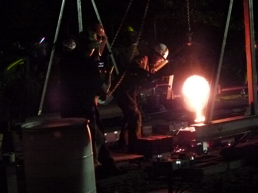 Pouring molten metal into a mold.