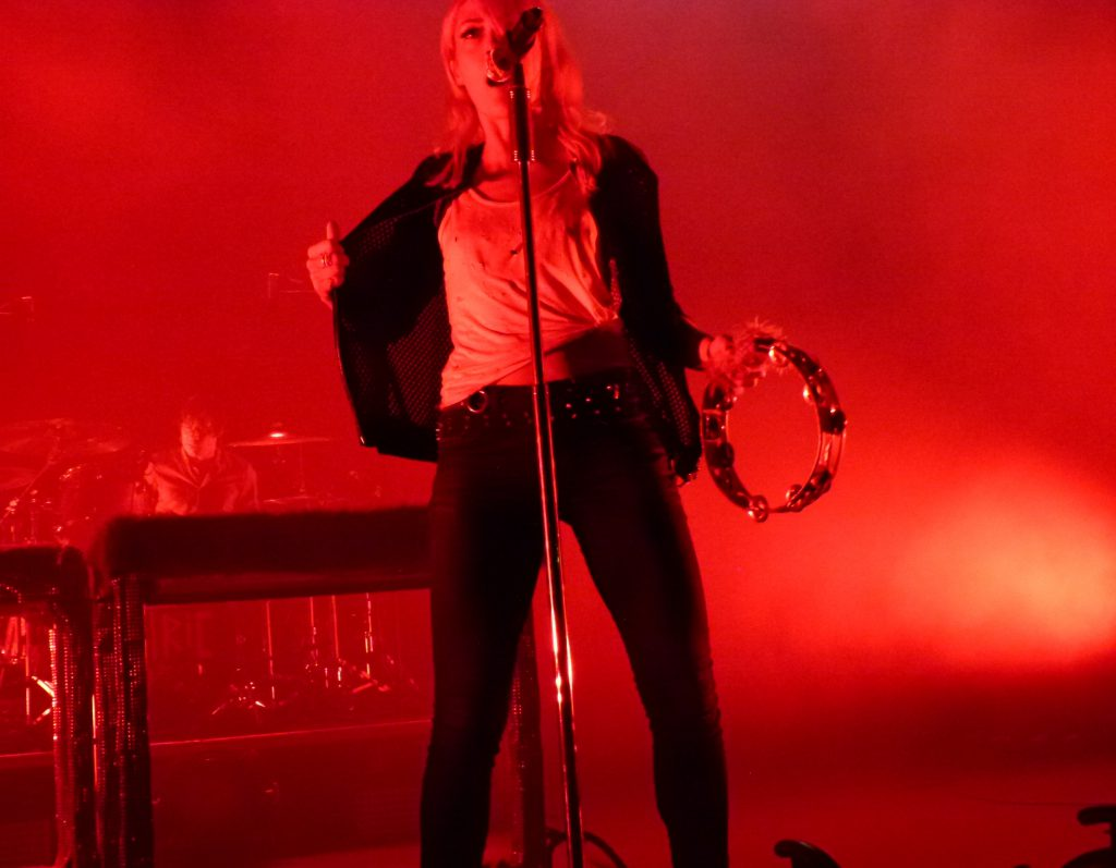 Emily Haines, bathed in red light, does a dance moving while singing and playing the tambourine.