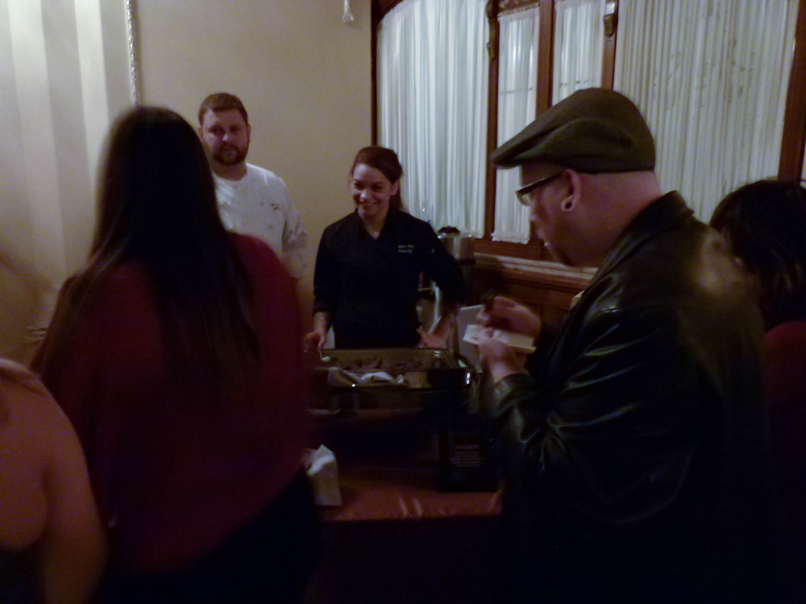 People line up for Valozzi's Chocolate Ravioli with Chocolate Ganache, Vanilla and Pomegranate served by Josiah Henry and Tabrina Avery.