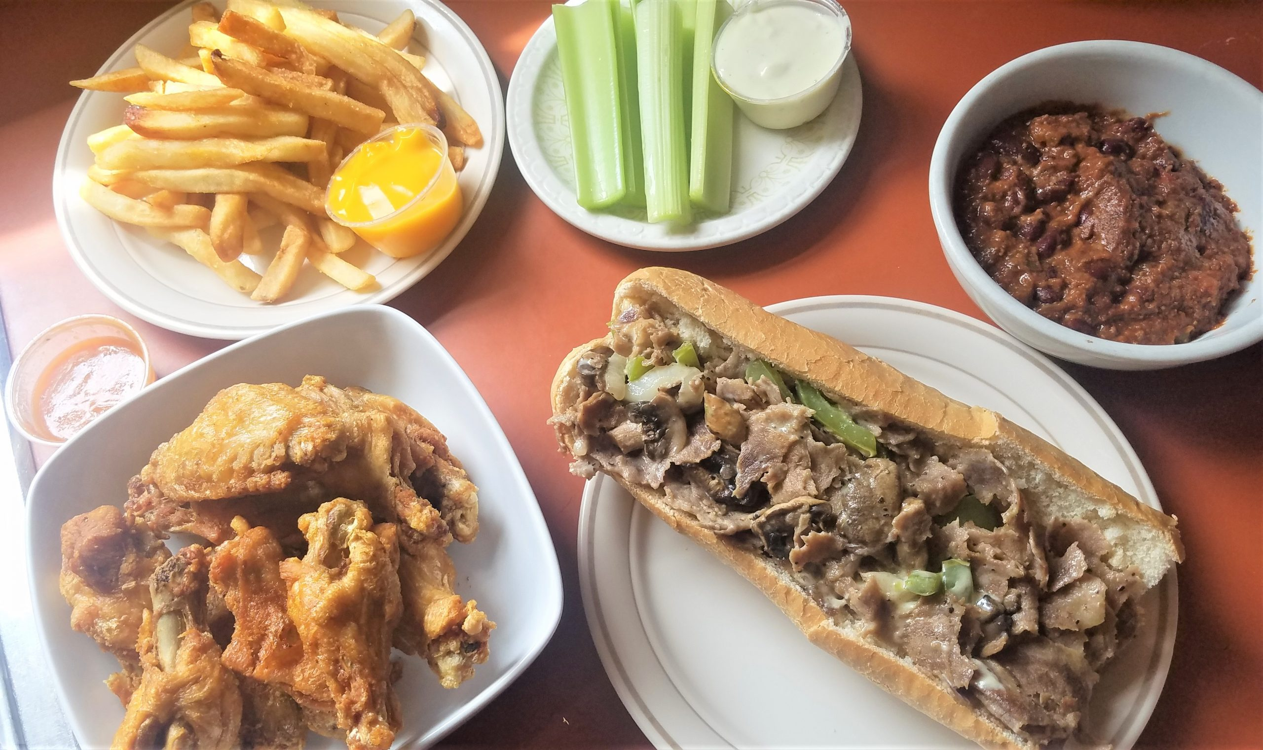A selection of popular items at the William Penn Tavern including chicken wings with kitchen sink sauce on the side, South Jersey cheese steak, chili, and french fries with cheese. (photo: Rick Handler)