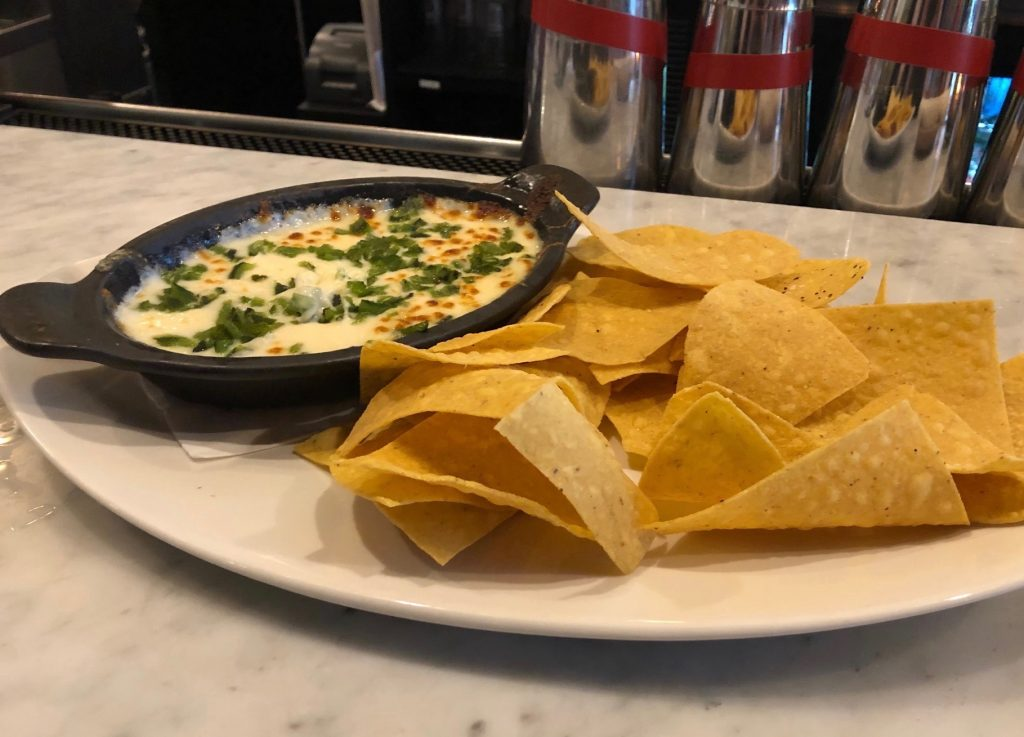 Poblano peppers add extra crunch to a bowl of queso blanco with chips.
