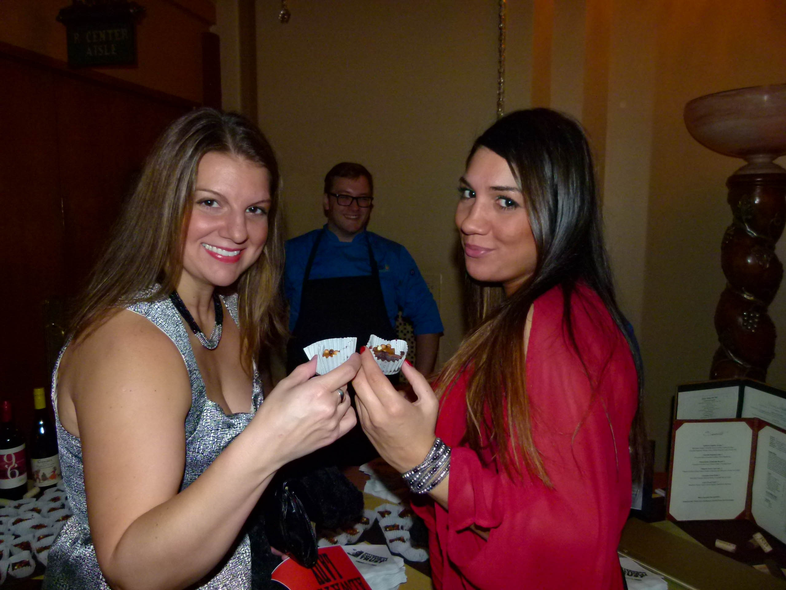 Women (and men) love chocolate, including Lisa Sipusic (L) and Alexarae Wehlau. They are ready to indulge in Flourless Chocolate Cake with Rich Dulce De Leche Cream and White, Milk, and Dark Chocolate Crisp Pearls from Sonoma Grill, as Scott Skaggs looks on.