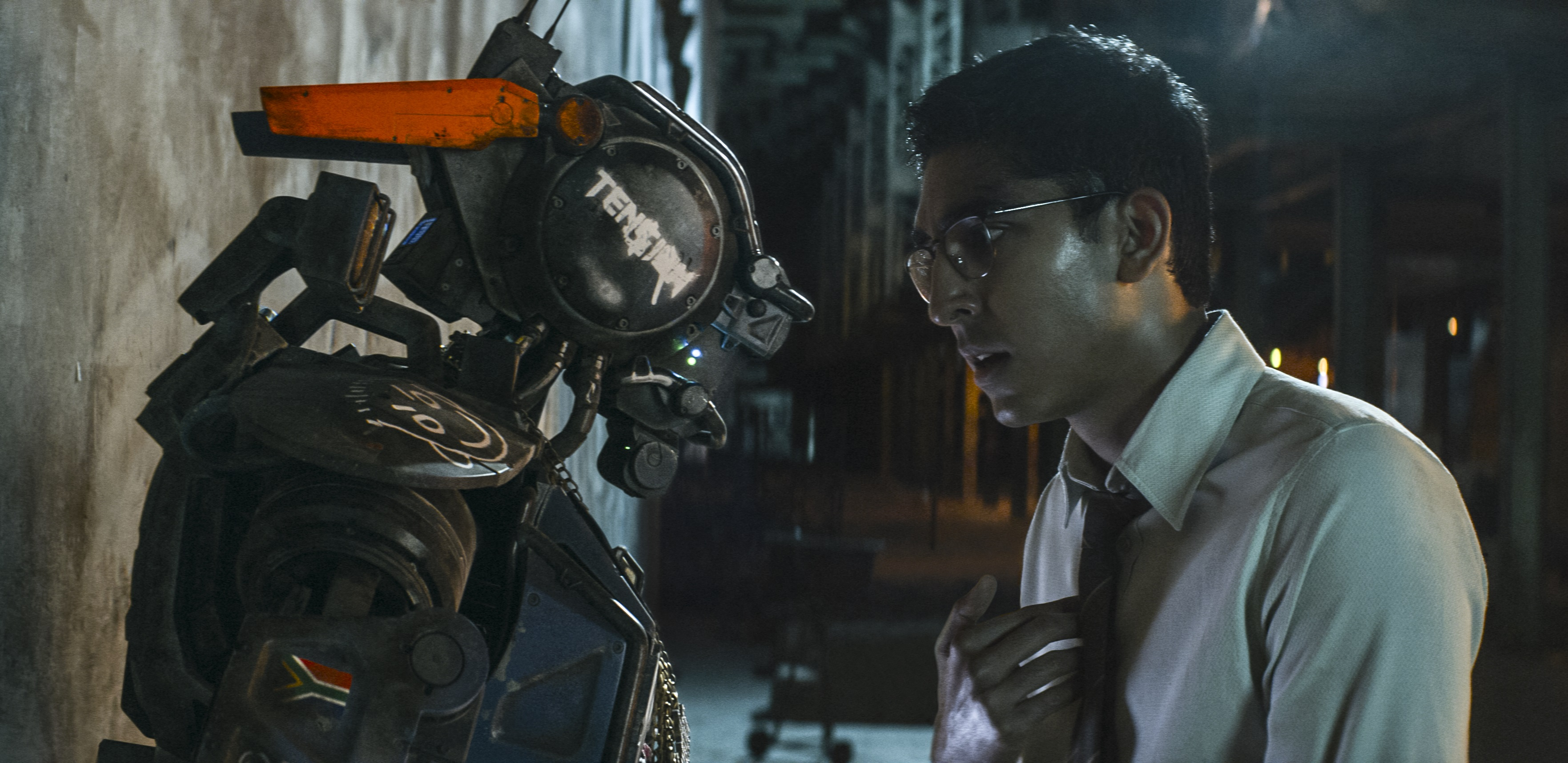Deon (Dev Patel) boots up Chappie with the new program.