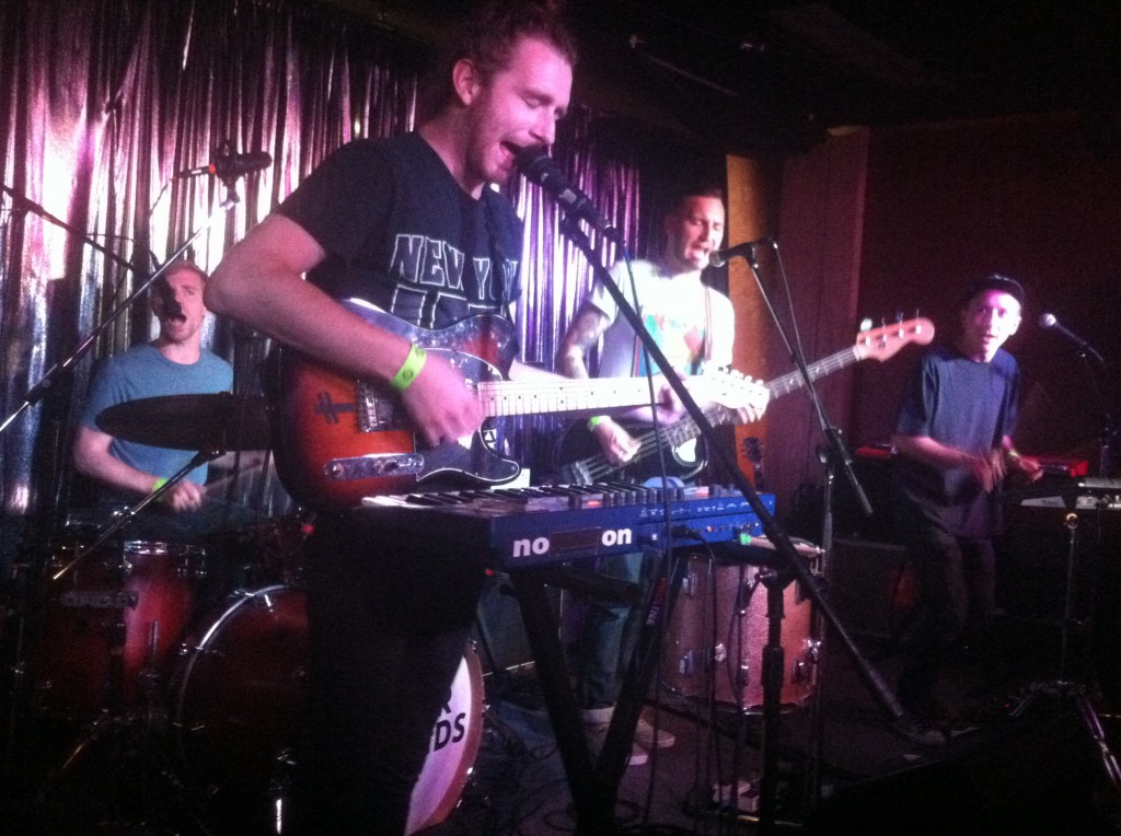 Dylan Rau singing and playing guitar with Val Loper (bass), Ted Feldman (guitar, keyboards), and TJ Orscher (drums).