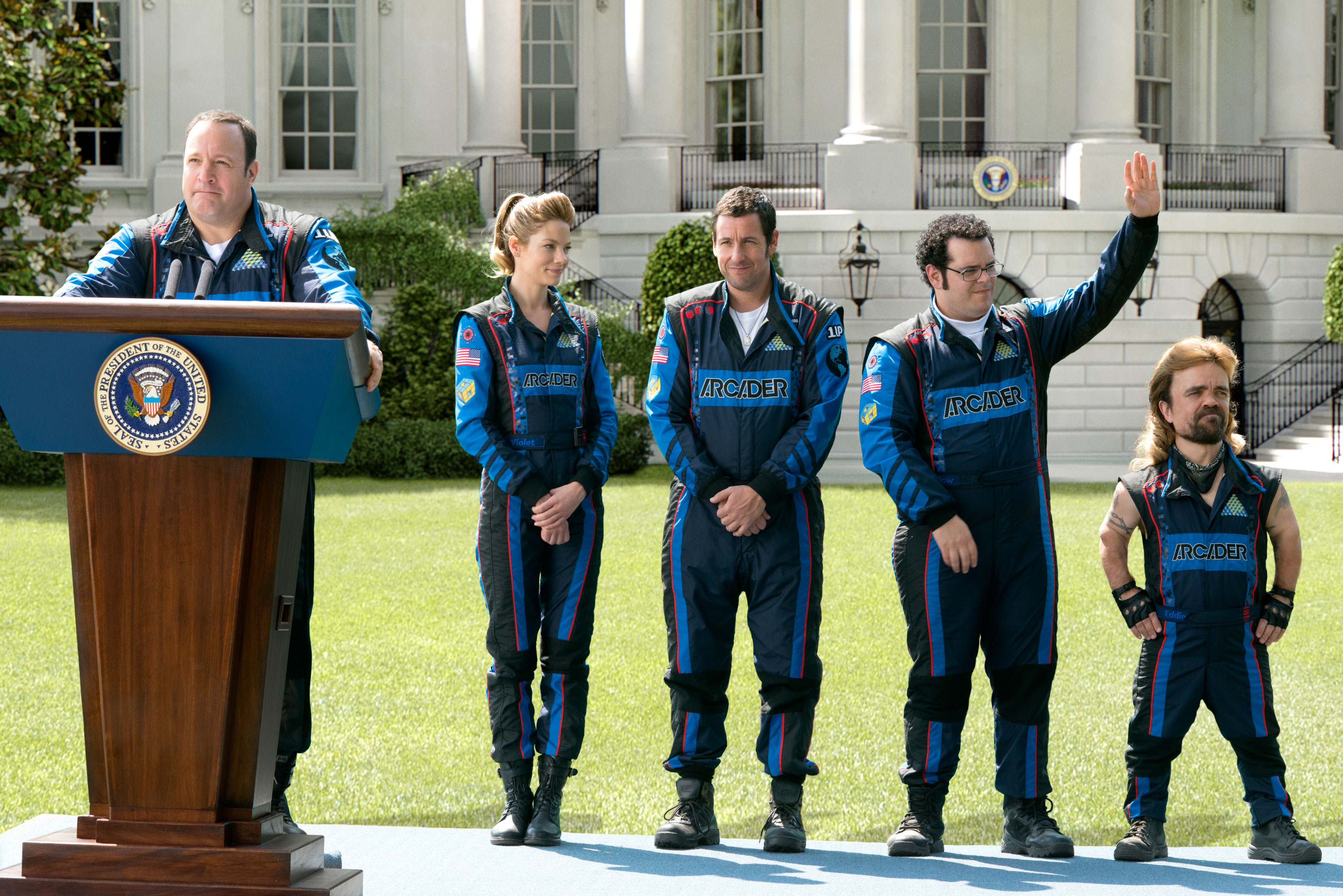 President Cooper (Kevin James) addresses the press on the White House lawn as Violet (Michelle Monaghan), Brenner (Adam Sandler), Ludlow (Josh Gad) and Eddie (Peter Dinklage) look on