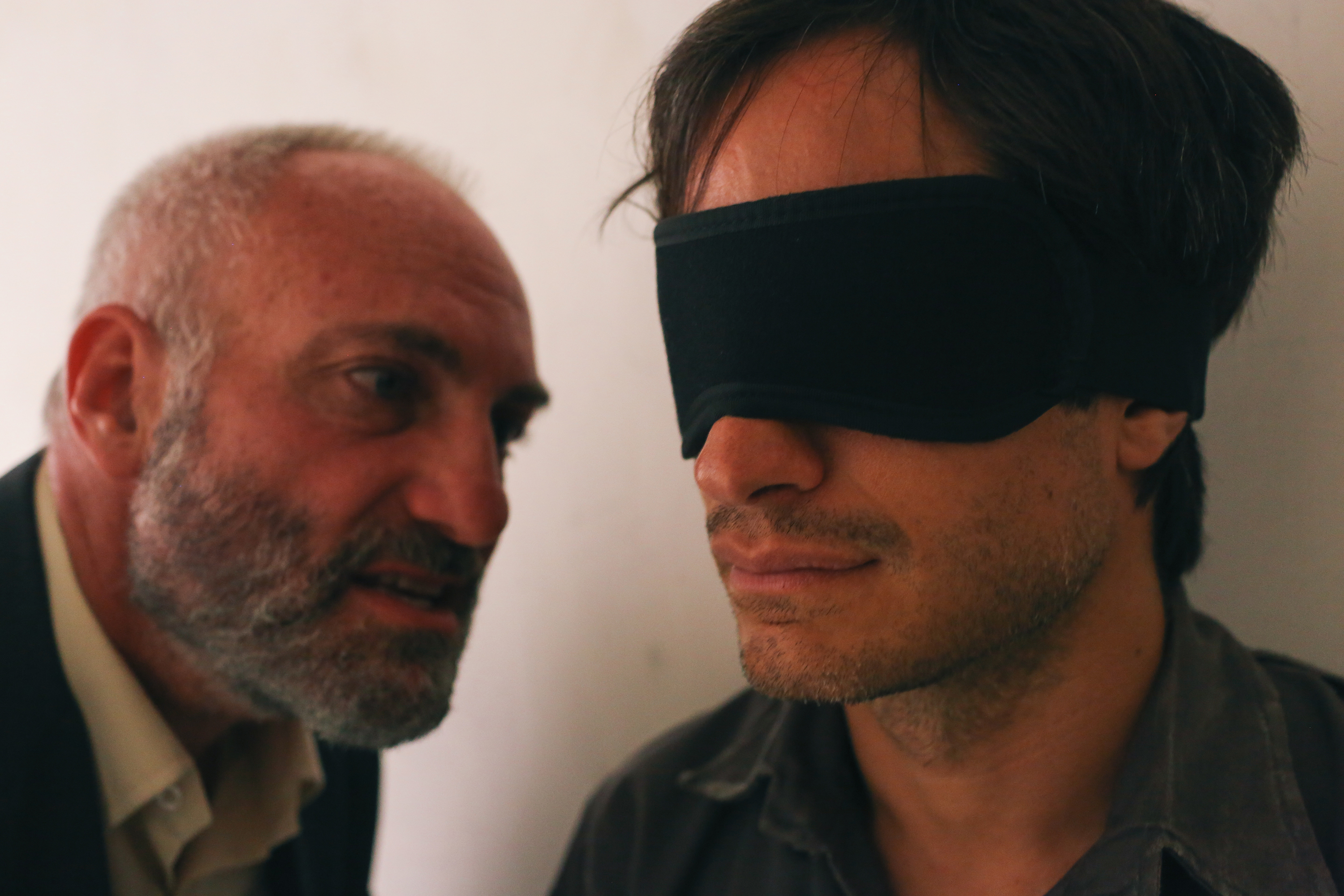 As Rosewater (Kim Bodnia, L) hammers away at the blindfolded Bahari (Gael Garcia Bernal), the question becomes: Who's really in the dark here? (Photo by Nasser Kalaji, courtesy of Open Road Films.)