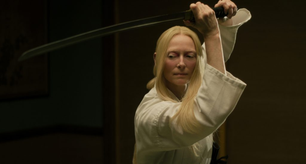 Tilda Swinton plays Zelda Winston the eccentric funeral parlor owner with good sword skills.