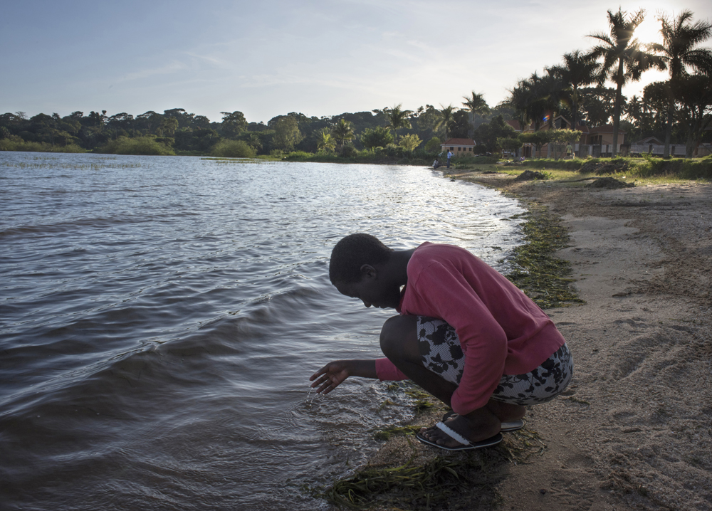 Rial's photos capture visions of hope: Jalia, a girl from the Bright Kids Uganda orphanage, contemplates the waters on an outing to Lake Victoria. She lost both parents to AIDS and her goal is to be a surgeon.