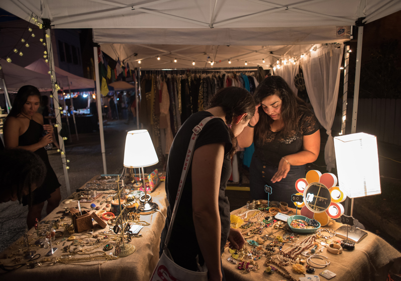 Marigrace Ambrosia (R) shares the story behind her collection of vintage jewelry for sale in a popup booth at the Garfield Night Market. Ambrosia and her colleague Sara Ponsoll are founders of Kitschtopia, an online vintage fashion store.